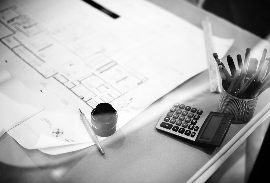 A black and white image of a calculator and pens sitting on house plans